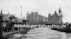Anleger am Baumwall; auf dem Ponton stehen Passagiere und warten auf ihr Schiff - ein Schild macht Werbung für die Hafenrundfahrt. Ein Schlepper zieht eine beladene Schute vom Hamburger Freihafen Richtung Elbe.