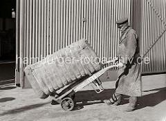Der Kaiarbeiter transportiert einen Ballen, der mit Bandeisen zusammengehalten wird auf seiner Sackkarre. Der Hafenarbeiter trägt seine Dienstmütze und eine Schürze zum Schutz seiner Kleidung; ca. 1934.