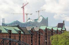 Kupfergedeckte Dächer und Giebeltürme der Backsteinarchitektur der historischen Hamburger Speicherstadt. Im Hintergrund das Dach und Baukräne an der Elbphilharmonie.