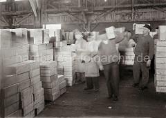 Die gelöschten Rosinenkisten sind am Hafenkai auf einen Transportwagen geladen worden - im Fruchtschuppen werden die Kisten von Hand abgeladen und von den Lagerarbeitern auf der Schulter zu dem Lagerplatz gebracht; ca. 1932.
