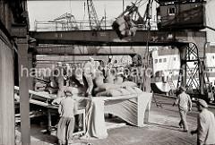 Eine Hieve Säcke schwebt über den Hafenarbeitern, die unter den Halbportalkranen vor dem Lagerschuppen arbeiten. Sie öffnen die Säcke und schütten den Inhalt auf ein Förderband; ca. 1934.