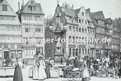 Marktgeschehen auf dem Messberg; Frauen mit Sonnenschirm und Kinderwagen, Bäuerinnen am Marktstand oder hinter Weidenkörben. In der Bildmitte der Vierländer Brunnen, dahinter die Fischerswtiete und die historische Bebauung der Hamburger Altstadt,