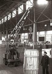 Eine große Holzkiste wird in einer der vielen Lagerhallen des Hamburger Hafens mit einem Laufkran transportiert. Vier Metallkrallen, die sich an der Eisenkette des Kranhakens befinden, tragen die Kiste.