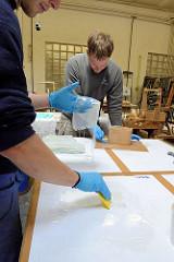 Stücke von Glasfasergewebe wird mit Epoxidharz eingestrichen.
