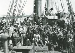Historische Fotografie - Arbeit im Hamburger Hafen früher - Gruppe Schauerleute, Hafenarbeiter auf einem Frachtschiff - Kohlenträger im Hamburger Hafen.
