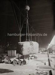 Mit einem speziellen Ladegeschirr für Wollballen setzt ein Hafenkran seine Ladung auf der Rampe ab; mit Eisenkrallen, die an einer Kette am Kranhaken hängt, wird der Ballen gehalten; ca. 1934.