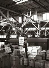 Mit dem fahrbaren Schuppenkran wird eine Holzkiste mit dem Kistengreifer im Lagerschuppen hochgehoben und auf andere Kisten gestapelt. Ein Lagerarbeiter manövriert die Last an den richten Platz.