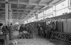 Lagerschuppen 37 im Hamburger Hafen / Segelschiffhafen; ein Förderband läuft entlang der in der Lagerhalle stehenden Güterwaggons, in die die Bananenstauden verladen werden.