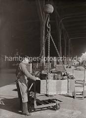 Holztonnen werden in einer Verladekiste vom Schiff an Land gebracht und dort auf eine Dreirad-Transportkarre gestellt. Damit bringt der Hafenarbeiter die Fässer an ihren Lagerplatz; ca. 1930.