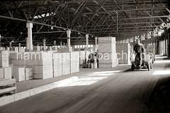 Ein Transportarbeiter fährt seine Ladung mit dem Elektrokarren und ihren Anhängern in den Lagerschuppen des Hamburger Hafens. Dort sind unterschiedlich grosse Holz-Kisten gestapelt, die auf ihren Weitertransport warten; ca. 1934.