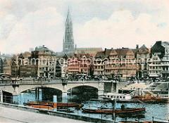 Die aus Stein gebaute Grosse Wandrahmsbrücke führt beim Oberhafen über den Zollkanal zum Messberg. Breite Steintreppen führen vom Anleger hinauf zur Strasse; im Vordergrund schleppt ein Hafenschlepper eine Schute in den Oberhafen. Hinter den