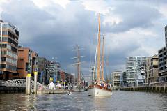 Traditionsschiffhafen in der Hamburger Hafencity - der Großsegler TOLKIEN liegt am Ponton, das Traditionssegelschiff FREDDY, Baujahr 1946,  fährt rückwärts zu seinem Liegeplatz.