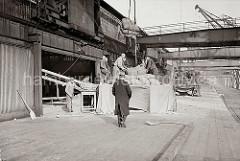 An den Toren der Lagerschuppen stehen die Hafenarbeiter auf einem Podest, die Ladung Säcke wird dort von den Hafenkränen abgeladen. Die Säcke werden auf einem Förderband geleert, die das Schüttgut in den Hafenschuppen transportieren; ca. 1934.