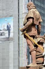 Skulptur Vasco da Gama auf der Kornhausbrücke, die über den Hamburger Zollkanal führt - Werbung an einer Hausfassade.