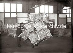 Ein Lagerarbeiter hat eine Vielzahl von Korbstühlen auf seine Karre gestapelt und fährt diese durch den Lagerschuppen im Hamburger Hafen. Im Hintergrund rechts stehen weitere unverpackte Sessel; rechts sind Säcke bei einer Waage gestapelt.