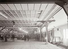Eisenbahnwaggons, die auf dem Gleis im Fruchtschuppen stehen werden mit Bananen beladen. Die Südfrüchte werden aus dem Lager mit Förderbändern transportiert - Arbeiter kontrollieren die Qualität der Ware; ca. 1932.