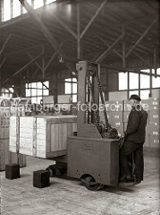 Mit einer Hubkarre der Herstellerfirma Amme Luther hebt ein Lagerarbeiter eine große Holzkiste an. Im Hintergrund sind weitere Kisten in dem Lagerschuppen des Hamburger Hafens gestapelt; ca. 1934.