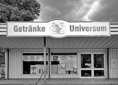 Schwarz-Weiss Fotografie - Laden in Dömitz / Elbe; Schild Getränke Universum - Atomsymbol, Umlaufbahn von Elektronen eines Atoms um den Kern - hier Bierglas.