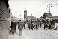 Kurz nach 17.00 Uhr strömen Hamburger Hafenarbeiter über den Vorplatz der St. Pauli Landungsbrücken - sie kommen von den Hafenfähren oder aus dem St. Pauli Elbtunnel. Einige fahren mit dem Fahrrad über das Kopfsteinpflaster.