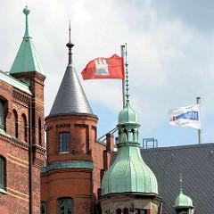 Türme der historischen Speicherstadt - Backsteinarchitektur und Kupferdächer - Hamburg / HHLA Fahne im Wind.