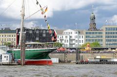 Heck vom Museumsschiff Rickmer Rickmers - Menschenmenge auf der Hafenpromenade; Kuppel vom Michel / Michaeliskirche.