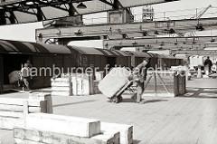 Ein Güterzug steht an einer Laderampe des Hamburger Hafens und wird von Hafenarbeitern entladen. Zwei der Arbeiter ziehen ihre Sackkarre mit einem grossen Ballen über die Rampe Richtung Lagerschuppen.