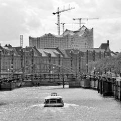 Ein Fahrgastschiff fährt auf dem Zollkanal Richtung Binnenhafen - Skyline der Hamburger Speicherstadt mit Elbphilharmonie.