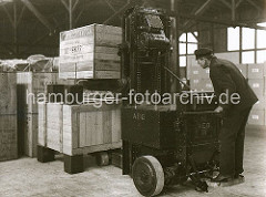 Der Lagerarbeiter stellt mit Hilfe eines Elektrohubkarrens eine grosse Holzkiste in einem Lagerschuppen des Hamburger Hafens ab; rechteckig Holzblöcke wurden als Abstandshalter zwischen den einzelnen Kisten verwendet.