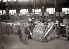 Von Hand setzen die Lagerarbeiter ein schweres Holzfass auf eine Transportkarre. Im Lagerraum des Hamburger Kaischuppens sind Tonnen und Säcke gelagert. ( ca. 1930 )