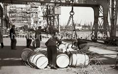 Hafenarbeiter schliessen das Transportnetz um eine Hieve Fässer, dann haken sie das Netz in die Kranhaken ein und die Ladung wird an Bord des Frachtschiffs gebracht. Im Hintergrund rollen Arbeiter die Holzfässer von Hand auf die Rampe.