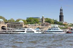 St. Pauli Landungsbrücken mit Fahrgastschiffen, die mit Touristen eine Hafenrundfahrt machen - re. der Kirchturm der St. Michaeliskirche / Michel.