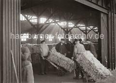 Kaiarbeiter transportieren dei Wollballen mit Sackkarren von der Laderampe in den Kaischuppen. Durch das Oberlicht des Lagerhauses fällt das Licht auf den mit Ballen gefüllten grossen Raum; ca. 1934.