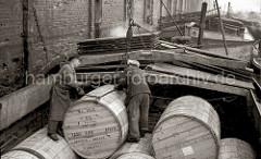Die grossen Holzfässer mit Tabak sind im Laderaum der Schute gestapelt. Zwei Arbeiter legen das Ladegeschirr am Fass an, damit es in den Laderaum des Lagerhaus G am Saalehafen gehoben werden kann.