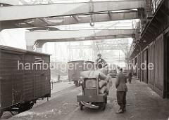 Der Hafenkran hat gerade eine Hieve Säcke auf dem Anhänger eines Elektrokarrens abgesetzt, die Ladung wird von Arbeitern vom Kranhaken gelöst. Auf dem Gleis vor dem Lagerschuppen stehen geschlossene Güterwaggons; ca. 1934.