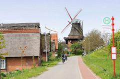 Wohnhäuser und Windmühle / Borsteler Mühle in  Jork, Altes Land - Radfahrer.