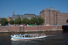 Blick über den Zollkanal Richtung Messberg. Auf dem Kanal fährt eine Barkasse der Hamburger Hafenrundfahrt mit Touristen an Bord. In der Bildmitte das Chilehaus, dahinter der Kirchturm der St. Jacobikirche; rechts das ehemalige Ballinhaus, jetzig