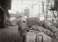 Der Führer eines Hafenkrans setzt eine Hieve Wollballen auf der Rampe des Kaischuppens ab; Kaiarbeiter dirigieren die Ladung an Land. Gebündelte Tierhäute liegen an der Rampe gestapelt, im Vordergrund der beladene Anhänger eines Elektrokarrens.