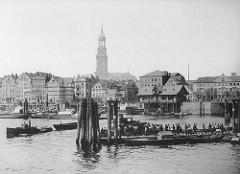 Blick über den Niederhafen zum Baumwall - Anleger am Kehrwieder; eine Barkasse zieht eine Schute - die Boote kommen vom Binnenhafen / Zollkanal - die Niederbaumbrücke ist re. zu erkennen - im Hintergrund der Turm der St. Michealiskirche.