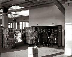 Fruchtkisten-Lager im ersten Stock des Fruchtschuppens. Links eine Sackkarre, mit denen einzelne Kisten transportiert werden - rechts werden hochbeladenen Transportwagen in den Fahrstuhl geschoben.