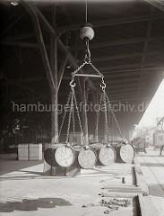 Vier Fässer hängen im Ladegeschirr des Hafenkrans über der Laderampe des Lagerschuppens. Im Hintergrund steht ein Lastwagen an der Rampe; ca. 1930.
