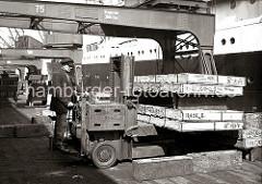 Arbeitserleichterung durch den Einsatz eines Akku-Hubstaplers der Herstellerfirma YALE auf einer Kaianlage des Hamburger Hafens. Der Fahrer stapelt große Holzkisten übereinander.