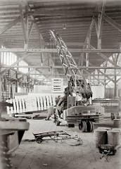Mit Hilfe eines fahrbaren Schuppenkrans der Herstellerfirma Lauchhammer wird eine sperrige Holzkiste an ihren Lagerplatz gehoben. Im Vordergrund liegt eine Sackkarre und auf einem Anhänger eines Elektrowagens liegen Holzblöcke.