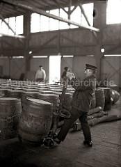 Ein Arbeiter setzt eine Holztonne auf die Selbstladekarre; mit Hilfe eines Eisenhakens wird das Fass auf die Sackkarre gezogen; ca. 1930.