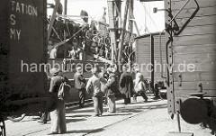 """Feierabend bei Arbeitern im Hamburger Hafen - die Hafenarbeiter verlassen über die Gangway den Frachter am Roßkai. Die meisten Männer tragen die typische Hamburger Schirmmütze, den """"Elbsegler"""" und einen Zampel."""