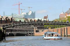 Eine Barkasse der Hamburger Hafenrundfahrt / Speicherstadtrundfahrt fährt auf dem Zollkanal unter der Jungfernbrücke - im Hintergrund die Kibbelstegbrücke und Kupferdächer der Speicherstadt sowie die Baustelle der Elbphilharmonie.