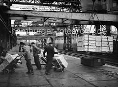 Die Apfelsinen werden vom Frachter gelöscht; der Kran stellt die Ladung auf dem Hafenkai ab. Auf dem Ausleger des Halbportalkrans ist die Tragkraft von 3000 kg. eingetragen - rechts sind die Laufräder des Krans auf der Schiene zu erkennen.