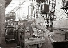 Hafenkräne löschen die Ladung eines Frachtschiffs - gebündelte Häute liegen auf dem Kaipflaster, eine Hieve mit Wollballen wird gerade auf der Laderampe abgesetzt. Im Vordergrund stehen Elektrokarren mit Anhänger, die auf die Beladung warten.