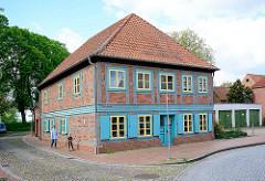Historisches Wohnhaus an der Fritz-Reuter-Strasse in Dömitz; blau abgesetzte Fensterluken, Tür; Kopfsteinpflaster Strasse Am Wall.