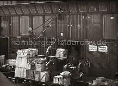 Pferdefuhrwerke stehen an der Laderampe eines Lagerschuppens im Hamburger Hafen; der Anhänger ist hoch mit Kisten und Ballen beladen. Ein fahrbarer Schuppenkran hebt gerade mit Hilfe eines Kistengreifers als Ladegeschirr eine Holzkiste.