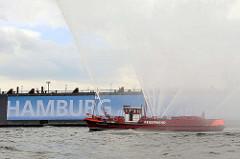 Feuerwehrlöschboot OBERBAURAT SCHMIDT - Wasserfontänen; Schriftzug Hamburg an der Wand vom Schwimmdock.